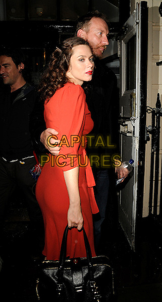 """ANNA FRIEL & DAVID THEWLIS .Departed after an evening performance of """"Breakfast At Tiffany's at the Theatre Royal Haymarket, London, .15th September 2009..half length black coat jeans moustache mustache facial hair water bottle beard couple red dress side sleeves black bag arm around waist .CAP/CAN.©Can Nguyen/Capital Pictures"""