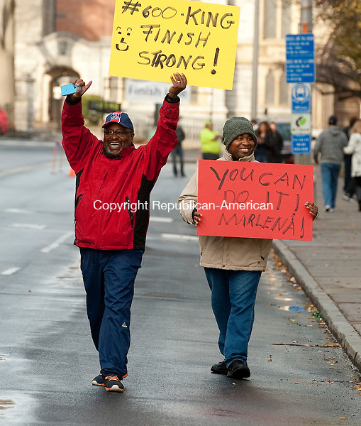 WATERBURY, CT--- -112215JS01--Runner Marlena Kind of Waterbury got some strong support from her father Dennis King, left and brother Jamaul King, right, as she runs her first road race during the annual Fischang-Cicchetti Road Race in Waterbury on Sunday. Jim Shannon Republican-American