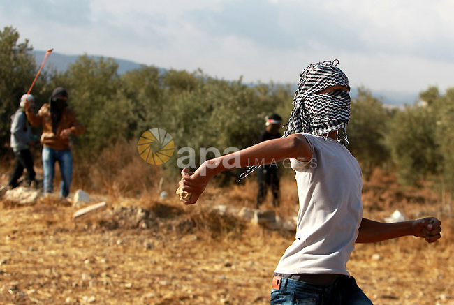 Palestinian protesters throw stones at Israeli security forces during clashes in the West Bank village of Tuqua, south-east of Bethlehem, on October 8, 2015. New violence rocked Israel and the Israeli occupied West Bank, including an incident in which men thought to be undercover Israeli police opened fire on Palestinian stone throwers they had infiltrated, wounding three of them. Photo by Muhesen Amren