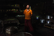A Buddhist monk poses for a photograph at the kitchen of the Diskit Monastery in Nubra Valley in Ladakh, India.