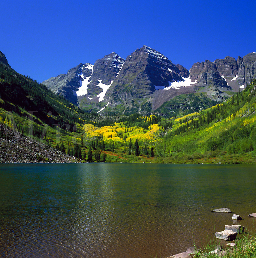 Scenic alpine landscape of mountains and a lake under a bright blue summer sky. Colorado.