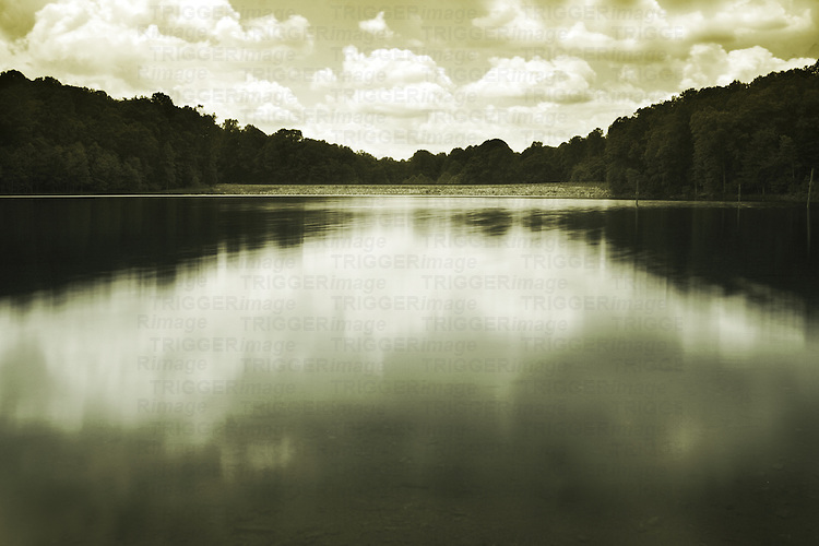 Still waters on a lake with trees and reflections