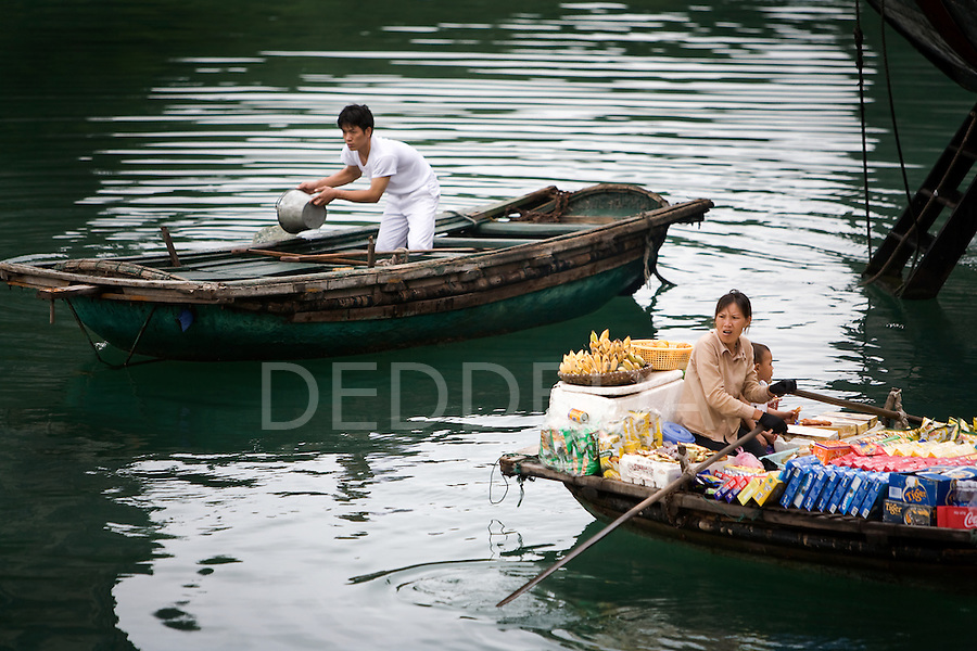 Local Vietnamese people working in boats in Halong Bay, Vietnam.