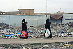Iraqi women covered head-to-toe in loose black cloaks,  full face veils and gloves carry shopping bags, as a boy accompanies them along a trash-strewn street in Mosul, Iraq. Such attire was relatively uncommon in Iraqi cities before the war, according to many residents, but insurgents have imposed strict Islamic dress and behavior codes in areas where they are strong. March 1, 2008. DREW BROWN/STARS AND STRIPES