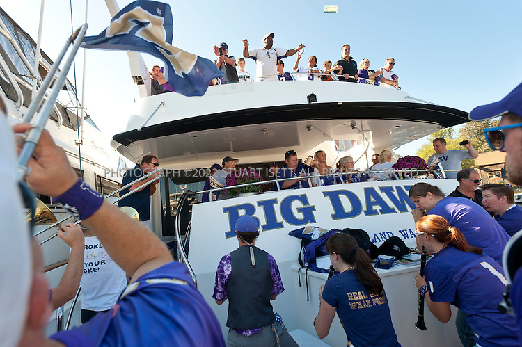 9/24/2011--Seattle, WA, USA...Members of the UW marching band perform on Big Dawg, parked at docks next to Husky Stadium...The 'Big Dawg', owned by Lisa and Tim Kittilsby, is the biggest, most prominent boat that attends regular boat tailgate parties on docks near the UW (University of Washington) Husky Stadium. Up to 500 boats will tie up outside Husky Stadium on football game days, ranging from from small boats to huge yachts. The Big Dawg is a 92-foot, two-story yacht that dominates the tailgate parties...The tradition started when Lisa and Tim Kittilsby's parents, Frank and Jeanie Miles, took a 23-foot boat called The Mixer to a game over 40 years ago...©2011 Stuart Isett. All rights reserved.