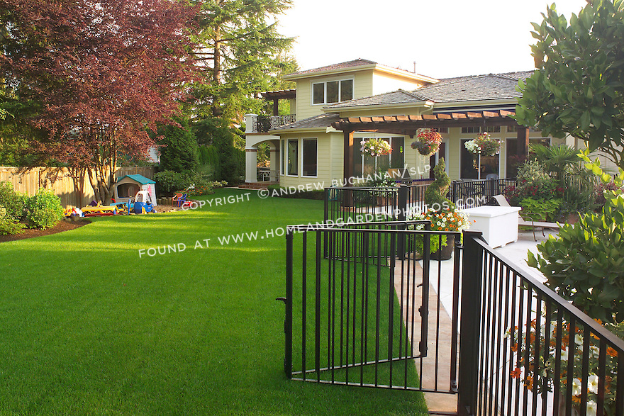 A wide shot of a suburban back yard at sunrise, showcasing a beautifully manicured, lush green lawn, a decorative patio bordered by an overhead arbor that hangs with baskets of colorful summer annuals, an attractive metal security fence surrounding a below ground swimming pool, and a kids' sandbox and play area.