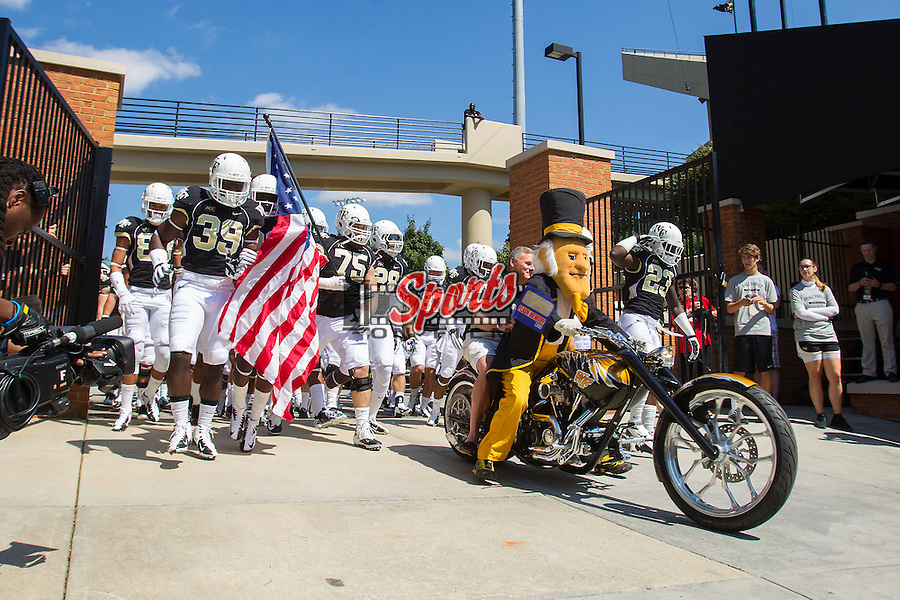 The Wake Forest Demon Deacon mascot and US Senator Richard Burr (NC-R) lead the football team onto the field prior to their game against the Louisiana-Monroe Warhawks at BB&T Field on September 14, 2012 in Winston-Salem, North Carolina.  The Warhawks defeated the Demon Deacons 21-19.    (Brian Westerholt/Sports On Film)
