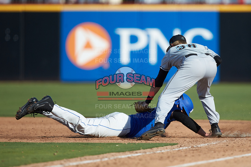 Walt Richardson (36) of the Coastal Carolina Chanticleers slaps a tag on Rudy Maxwell (26) of the Duke Blue Devils as he dives back into first base at Segra Stadium on November 2, 2019 in Fayetteville, North Carolina. (Brian Westerholt/Four Seam Images)