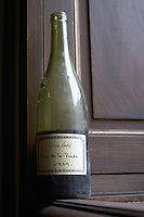 A half empty dusty old bottle with a hand written label saying Louis Jadot Clos de la Roche 1979 Grand Cru Burgundy red wine side-lit side light, closeup on a window sill, Maison Louis Jadot, Beaune Côte Cote d Or Bourgogne Burgundy Burgundian France French Europe European