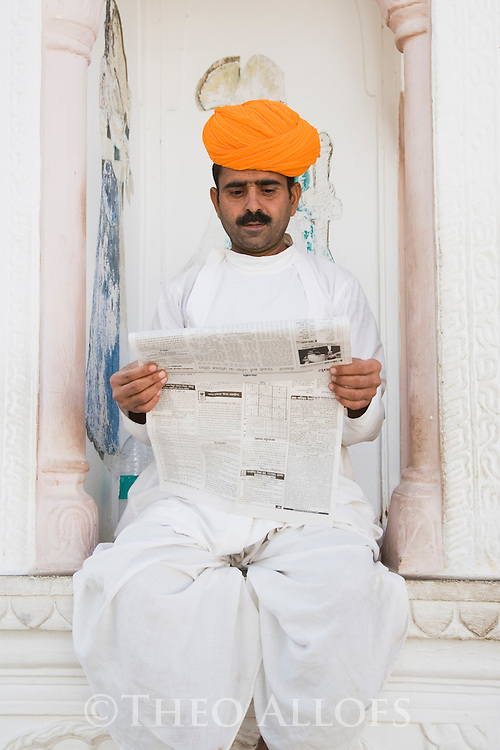 Rajasthani man reading newspaper in front of hotel in Pushkar, Pushkar, Rajasthan, India --- Model Released
