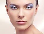 Closeup beauty portrait of a young woman face with soft pastel blue color makeup