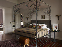 The Casamidy designed canopy bed has a velvet headboard and a vaulting horse serves as a bench