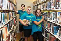 Donovan Montville,'21, Adam DaSilva,'21, and Sophia Lusignan organize books at the Redwood Library as they participate in the Salve Regina University Exploration Day of Service in Newport.