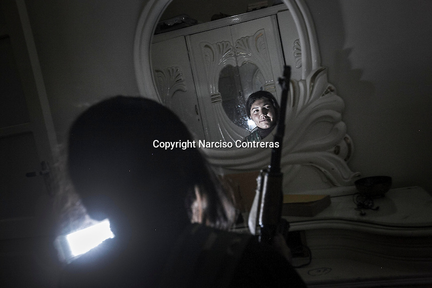 A Kurdish female fighter is seen reflected in a mirror bedroom inside an abandoned building used by Kurdish rebels as temporary dormitory in the majority-Kurdish Sheikh Maksoud district of the northern Syrian city of Aleppo, during the clashes after Syrian opposition fighters entered into the Kurdish area forcing thousands of civilians to flee into safe areas outside of Aleppo City. Since then, the neighborhood is being bombed and shelled by Syrian forces in its attempt to sweep out the opposition fighters from the area.