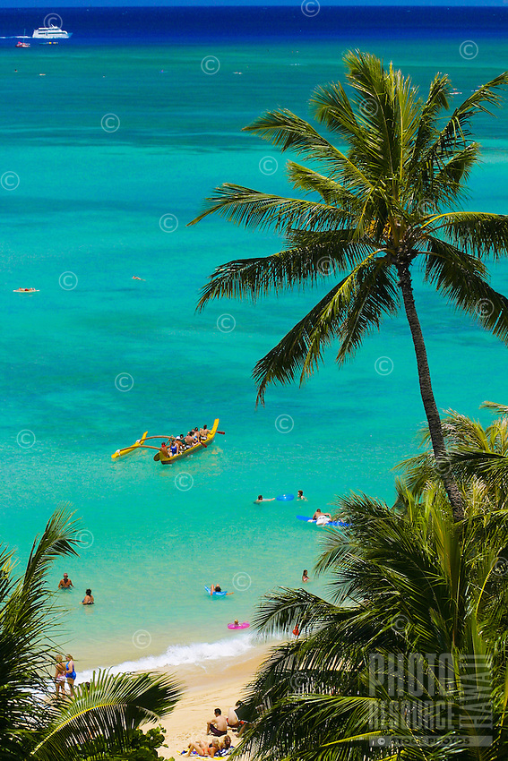 Vacationing tourists enjoy a ride in an outrigger canoe off of scenic Waikiki Beach, Oahu.