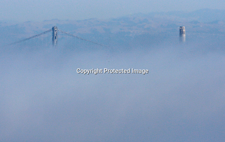 San Francisco's fog underlines Coit Tower and the Bay Bridge as seen from the Marin headlands from  Sausalito, California.