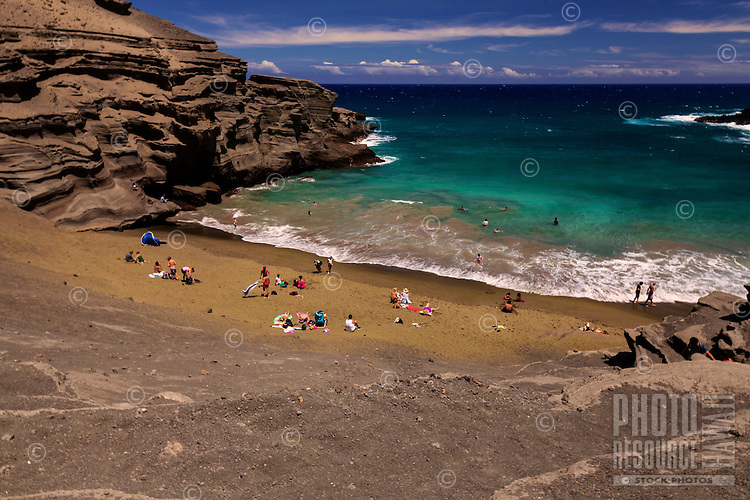 Visitors enjoy Papakōlea Beach (also known as Green Sand Beach or Mahana Beach), a green sand beach near South Point on the Big Island of Hawai'i.