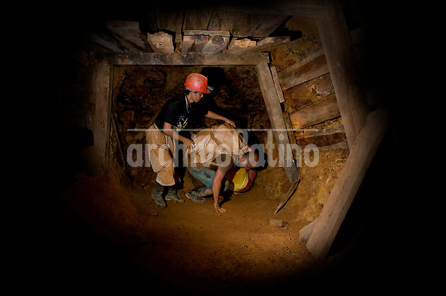 Illegal miners manually take out  a sack full of rocks from an underground gallery in  Segovia, Antioquia, Colombia