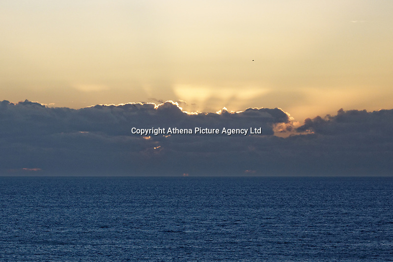 The sun sets behind low lying clouds in the horizon off Rhossili near Swansea, Wales, UK. Saturday 05 February 2019