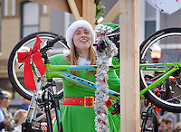 STAFF PHOTO BEN GOFF  @NWABenGoff -- 12/13/14 Rachel Evans rides on the Phat Tire Bike Shop float during the Bentonville Christmas parade through downtown on Saturday Dec. 13, 2014.