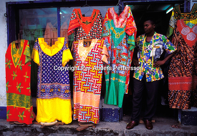 dicocon00175 .Congo. Kinshasa. Business. Retail. Sylla Amara, a tailor outside his shop (called Mandino) with his work on February 28, 2002 in a busy street in central Kinshasa, Congo.  The shirts are typical Congolese, but also makes West African shirts for clients. Especially women come to buy his clothes and his clientele includes people from Zimbabwe, Mali and Togo. Traditional dress..©Per-Anders Pettersson/iAfrika Photos