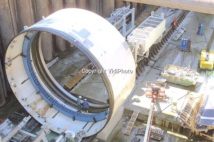 Foto: VidiPhoto..ANGEREN - In de 20 meter diepe boorput bij het Pannerdensch Kanaal is begonnen met de bouw van een enorme boorkop. De kop, met een diameter van 9,80 meter en een lengte van 72 meter, moet in oktober kunnen starten met het boren van de tunnel voor de Betuwelijn onder het Pannerdensch Kanaal door. De totale lengte van de tunnel is 2680 meter, waarvan 1600 meter geboord gaat worden. In 2004 moet de tunnel klaar zijn.