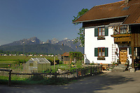 White house with green shutters, balcony and greenhouse in fenced garden with the background of the Alps.<br /> Near Forgensee lake, Schwangau, Bavaria, Germany.