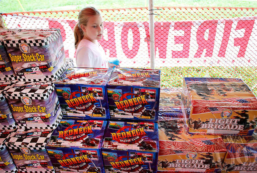 NWA Media/DAVID GOTTSCHALK - 6/23/14 - Kelsie Engle, 7, takes a quick survey of the fireworks at Hale's Fireworks Stand in Farmington Monday June 23, 2014 following a brief rain storm. The stand, which features a variety of fireworks including bottle rockets, mortar shells and family packs, is open from 6:30 a.m. to 12:00 a.m. daily through July 6, 2014.