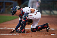 Mississippi Braves catcher Matt Kennelly (14) cleans up home plate area during a game against the Pensacola Blue Wahoos on May 27, 2015 at Trustmark Park in Pearl, Mississippi.  Pensacola defeated Mississippi 7-5 in fourteen innings.  (Mike Janes/Four Seam Images)