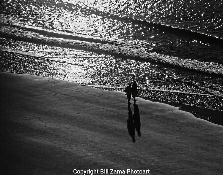 Couple strolling on Myrtle Beach at sunrise in black & white format.