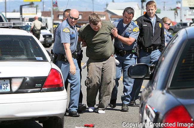 Washington State Patrol troopers along with officers with the CWU Campus Police take a motorist into custody after a standoff along Canyon Road in Ellensburg, Friday, June 7, 2013.  The standoff came to a close when the motorist suddenly drove away forcing the officers into a short chase ending with his arrest near the intersection of Canyon Road and Mountainview Avenue. (Brian Myrick / Daily Record)