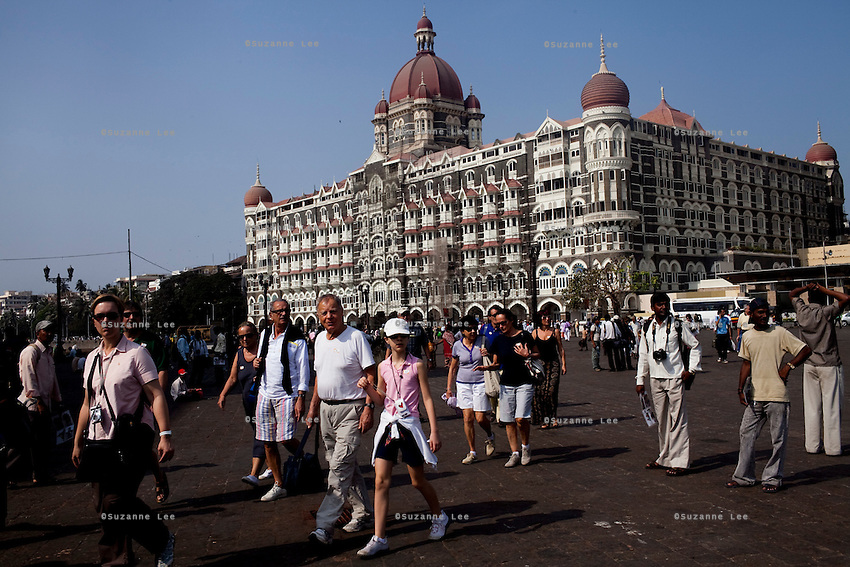 Tourists walk past the Taj hotel's old building that was attacked in the Mumbai 26/11 in year 2008 faces the Arabian sea on the Marine Drive in Mumbai, India. Photo by Suzanne Lee