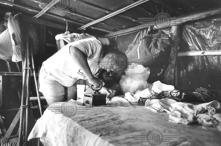 © Paul Smith / Panos Pictures..Sao Paulo State, BRAZIL..A woman ironing her daughter's clothes in the wooden shack, or barracao, in which they live by the side of a road.
