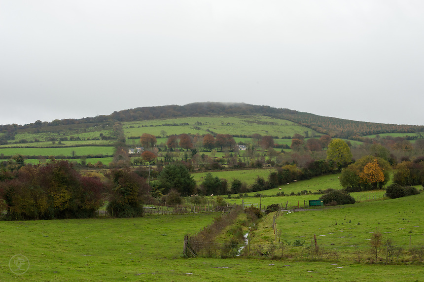 The Slieve Bloom Mountains with green pasture in the foreground on a cloudy autumn day, Ireland.