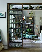 The clever use of a glass shelving partition both connects and separates the sitting room from the adjoining kitchen