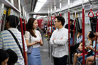 HONG KONG - MAY 05: Beverly Chung and Keith Cheung chat in the subway, on May 5, in Hong Kong. (Photo by Lucas Schifres/Pictobank)