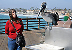 Ginny Christensen, relating to a Pelican, perched near a fish cleaning station along the Oceanside Pier, on visit to Oceanside, CA, on Wednesday, April 27, 2016. Photo by Jim Peppler. Copyright Jim Peppler  2016.