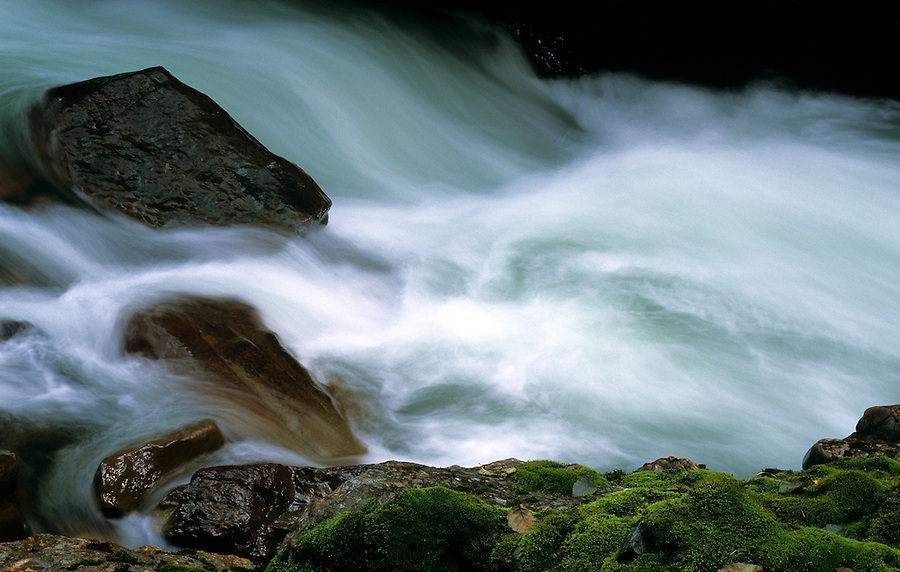 A long exposure along the shore of the Nooksack river reveals white tendrils as the water flows swiftly over the rocks.