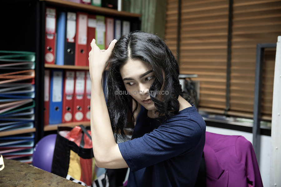 Bee, a transgender model at Apple Model Managemnt fixers her hair before a quick shoot in the office to update her measurements.<br /> <br /> Bangkok, Thailand 2015 © Giulio Di Sturco