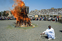 Eritrea. Asmara.                                                                   September square.                                                                                  Meskel is the most important religious feast for the orthodox church in Eritrea. It takes place every year on september 27.                                                                                                                                            A man dressed in white cotton loinclothes kneels near the burning woodshed, which has a white holy cross on its top.  Once fully burned, the crowd will run to the furnace, collect some unburn wood parts and pick up ashes to draw a holy black cross on their foreheads.   © 2002 Didier Ruef