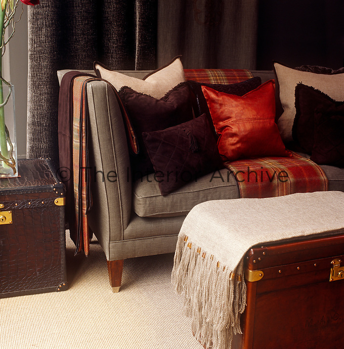 On the sofa of a London living room a red woollen tartan throw and red leather cushion create a note of contrast amongst suede and linen cushions in tones of brown and beige