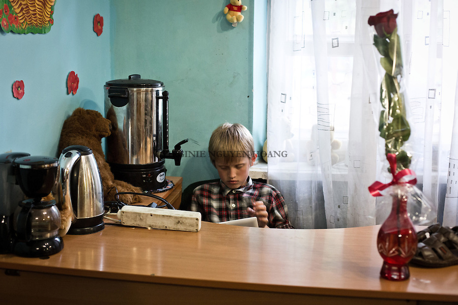 """UKRAINE, Mariupol: A young boy living in Piligrim is reading a book. As the center is owned by pastors of the congragation """"The Church of the good chance"""", children are under a daily christian education."""