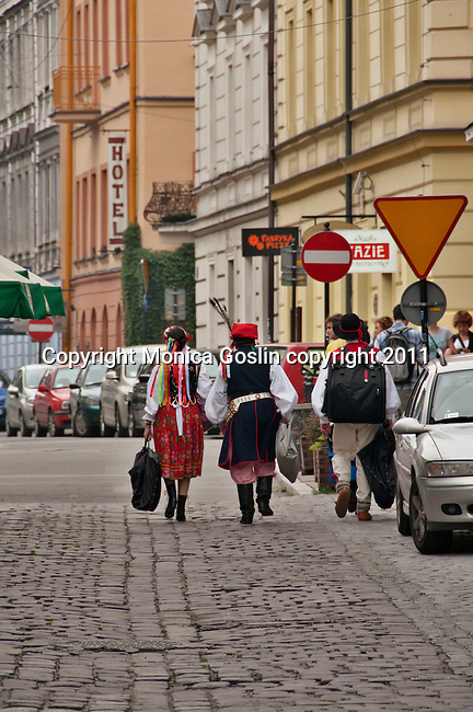 A group of musicians and dancers in traditional costumes, walking down a street in the Jewish Quarter of Krakow, Poland