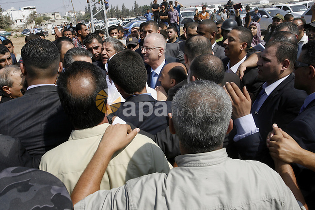 Palestinian Prime Minister Rami Hamdallah speaks to residents as he visits the al-Shijaiyah neighborhood in the east of Gaza city on October 9, 2014. The Palestinian unity government which took the oath of office in June under technocrat prime minister Rami Hamdallah arrived to Gaza Strip on Thursday to convene the first fully meeting. Hamdallah said that the unity government will rebuild the bombed-out Gaza Strip following a seven-week Israeli offensive. Photo by Abed Rahim Khatib