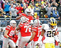 Ohio State Buckeyes quarterback J.T. Barrett (16) celebrates his touchdown run in the arms of Ohio State Buckeyes offensive lineman Darryl Baldwin (76) against Michigan Wolverines in the 2nd quarter of their game at Ohio Stadium in Columbus, Ohio on November 29, 2014.  (Dispatch photo by Kyle Robertson)