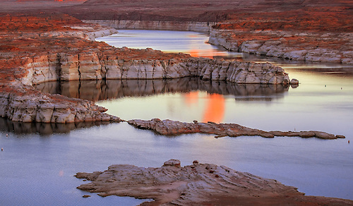 The landscape at Lake Powell is reflected in its waters at sunset.