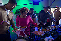 NWA Democrat-Gazette/CHARLIE KAIJO Guests serve themselves food from a buffet line on Monday, January 1, 2018 at the World Event Center in Rogers. The event Trappy New Year is a New Years day party started by Angie Henry of Bentonville, a radio host on KDIV 98.7. <br />