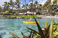 Caucasian man and boy kayaking in lagoon at Grand Hyatt Kaua'i Resort in Koloa, Kaua'i