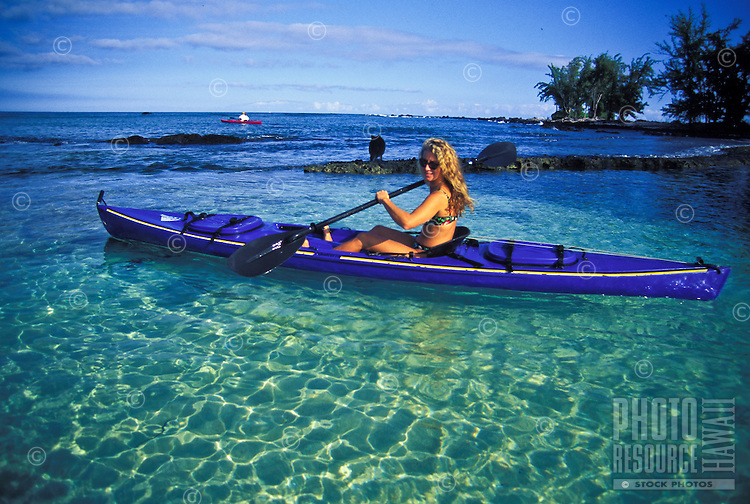 Young woman kayaks at Makalawena Beach, Kona Coast, Big Island of Hawaii