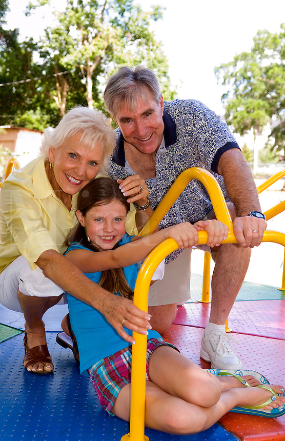 Grandparents with granddaughter family having fun outdoors in park on colorful ride with love and caring